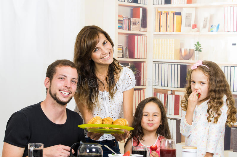 Portrait of happy family eating breakfast. Portrait of young happy family eating breakfast royalty free stock image