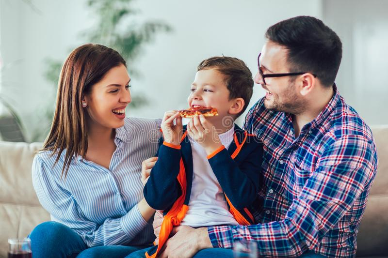 Happy family eating pizza while sitting on sofa at home. Portrait of happy family eating pizza while sitting on sofa at home stock photo