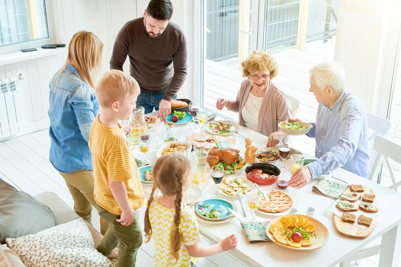 Festive Family Dinner in Sunlight. Portrait of happy family enjoying dinner together sitting at table with delicious dishes, focus two grandparents smiling stock photo