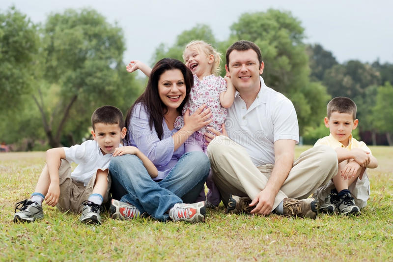 Portrait of happy family of five on the green land. Over natural background stock photography