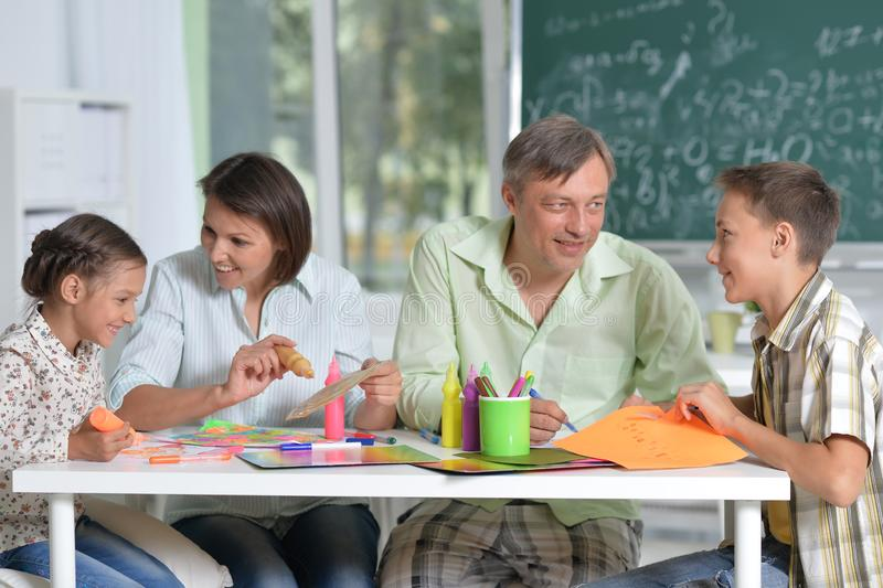 Portrait of happy family of four drawing together at home royalty free stock photography