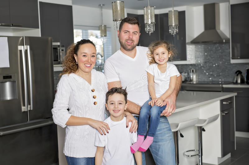 Portrait of a happy family of four in the kitchen at home royalty free stock images