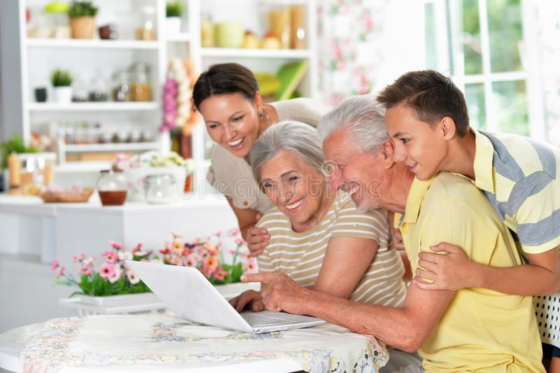 Portrait of happy family with laptop at kitchen royalty free stock photo