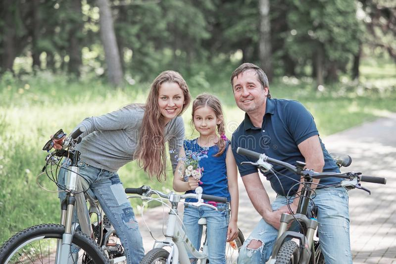 Portrait of a happy family with a little daughter on a bike ride royalty free stock photo