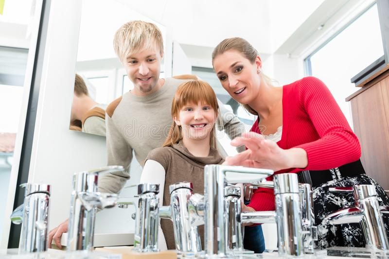 Portrait of a happy family looking for a new bathroom sink faucet. Low-angle portrait of a happy family, looking for a new bathroom sink faucet in a modern stock photos