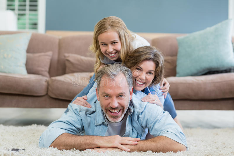 Portrait of happy family lying heaped on carpet in living room stock image
