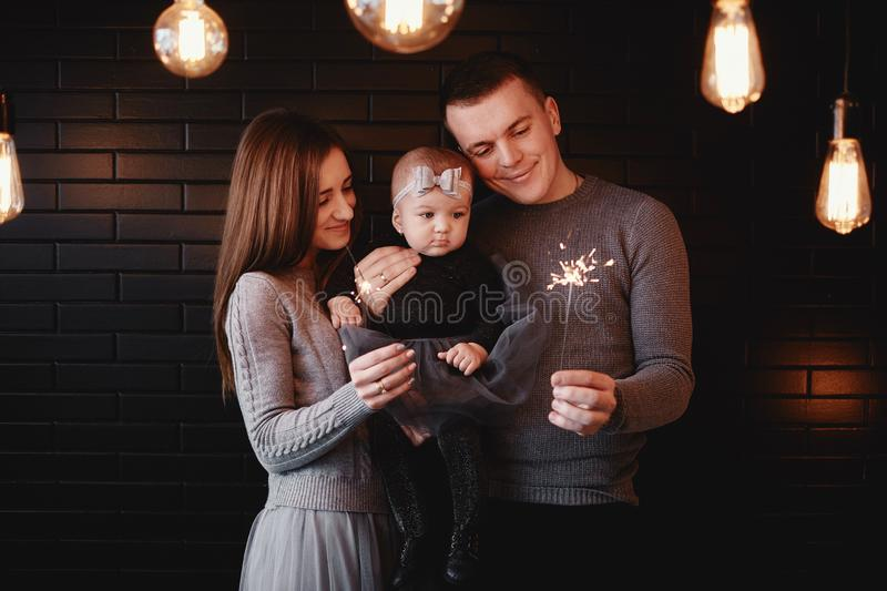 Portrait of happy family, mom, dad and baby girl with sparklers in front. family in anticipation of Christmas royalty free stock photo