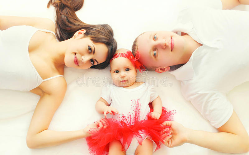 Portrait happy family mother, father and baby lying on the bed stock photos
