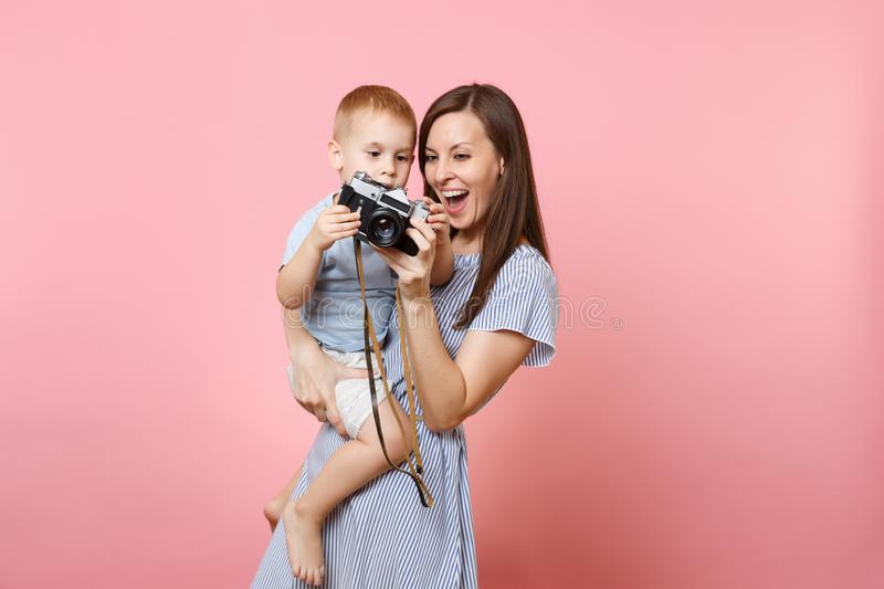 Portrait of happy family. Mother keep in arms, have fun, hug son baby boy, take picture on retro vintage photo camera on stock image