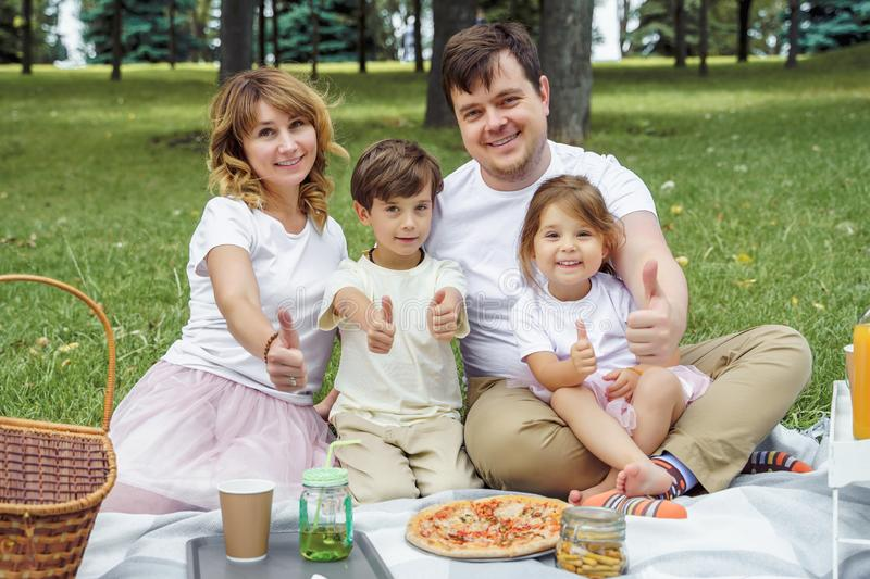 Portrait of happy family showing thumbs up at picnic stock image