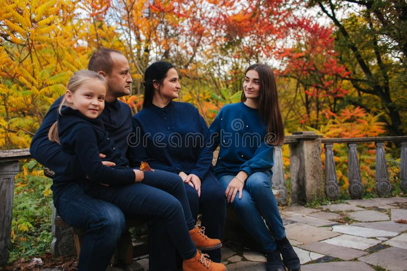 Portrait of happy family sitting on the bench in the forest. Autumn weather and colorful trees.  royalty free stock images