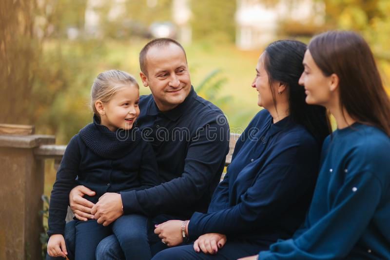 Portrait of happy family sitting on the bench in the forest. Autumn weather and colorful trees.  royalty free stock image