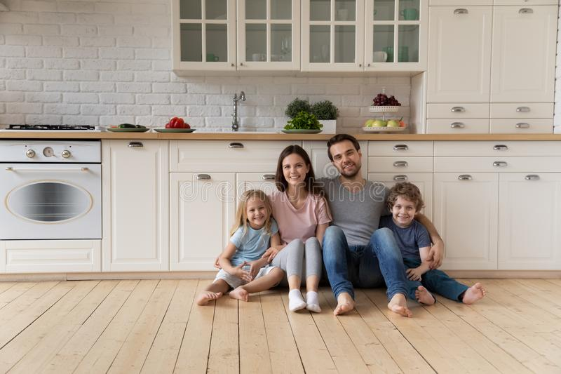 Portrait of happy family sitting on floor at kitchen. stock images