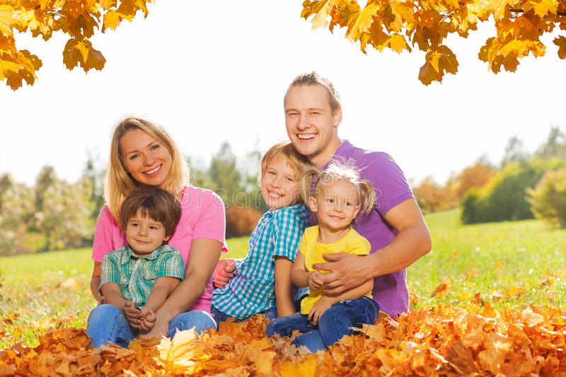 Portrait of happy family sitting on the leaves royalty free stock photos