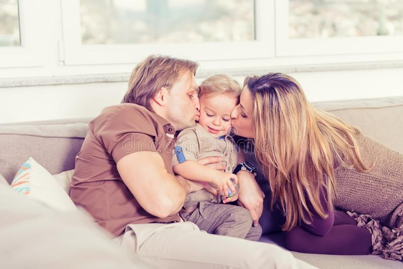 Portrait of happy family sitting on the sofa and playing. Parents kissing their baby son royalty free stock photos