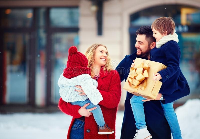 Portrait of happy family at snowy winter street, christmas holidays stock photos