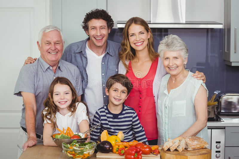 Portrait of happy family standing in kitchen stock photo