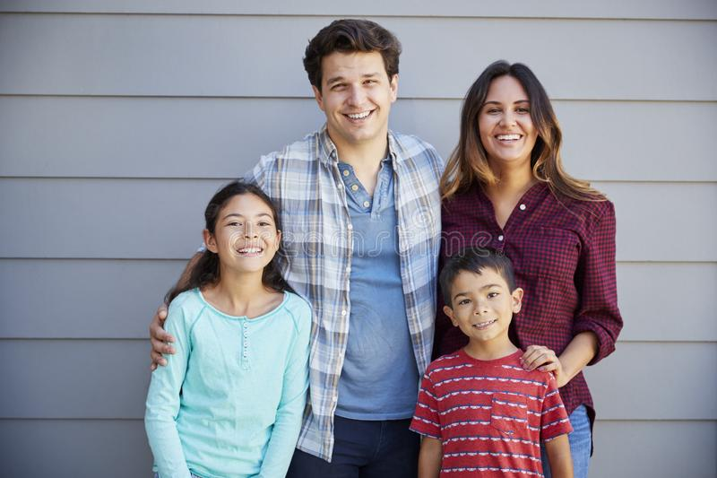 Portrait Of Happy Family Standing Outside Grey Clapboard House stock photos