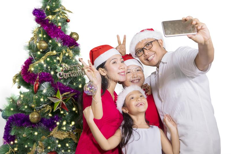 Happy family taking selfie with Christmas tree royalty free stock image