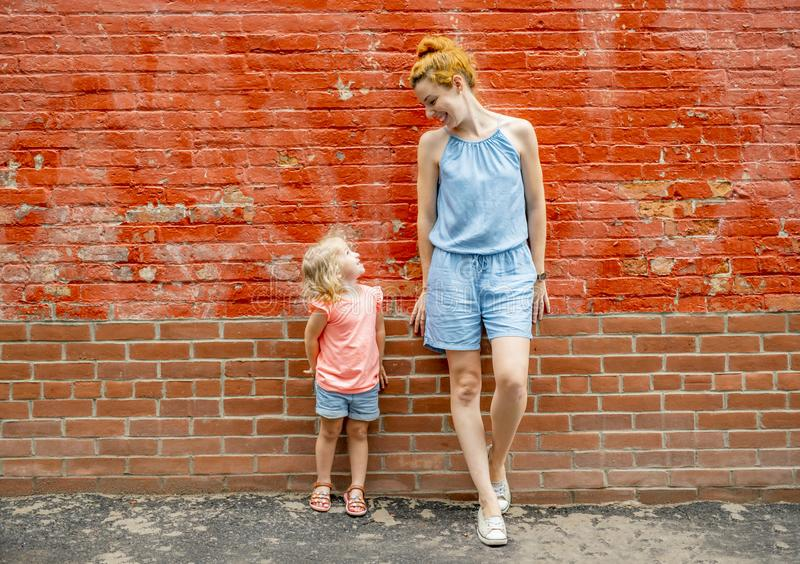 Portrait of a happy family a young beautiful woman with her little cute daughter standing near brick wall. stock photos