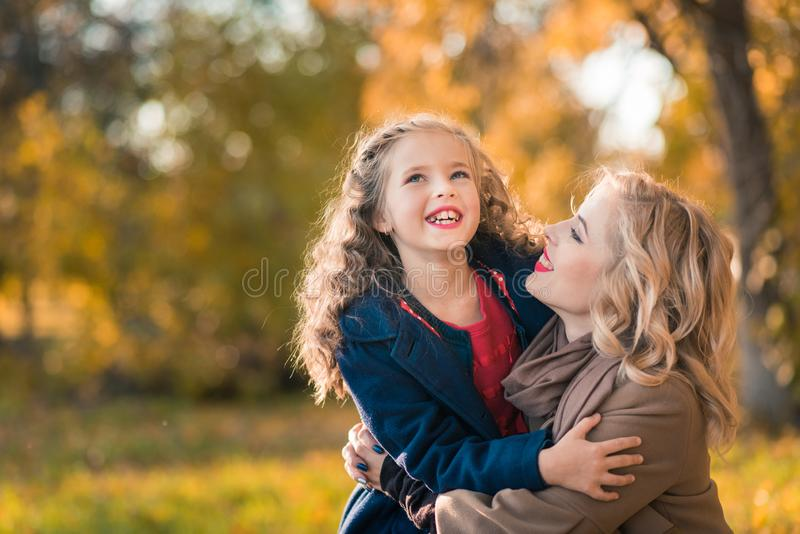 Happy joyful woman having fun with her girl in autumn color royalty free stock images