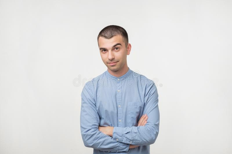 Portrait of happy fashionable handsome man in blue shirt crossing hands and look at camera. royalty free stock photo