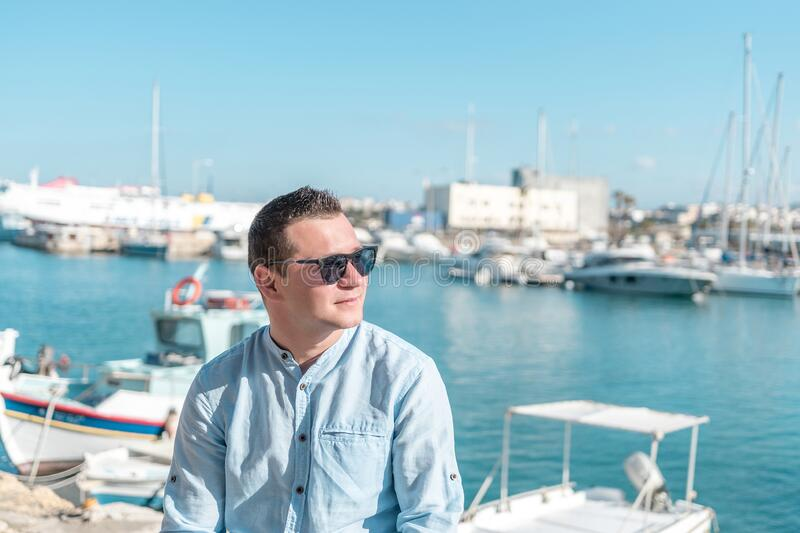 Portrait of happy fashionable handsome man in blue shirt in the harbour royalty free stock photography
