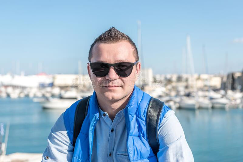 Portrait of happy fashionable handsome man in blue shirt in the harbour royalty free stock photo