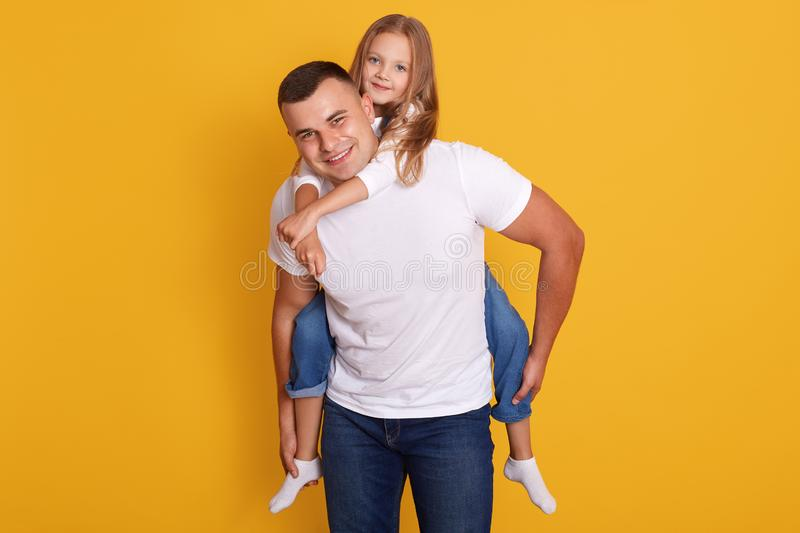 Portrait of happy father and beautiful little girl wering white t shirts and jeans, posing isolated over yellow studio background royalty free stock photography