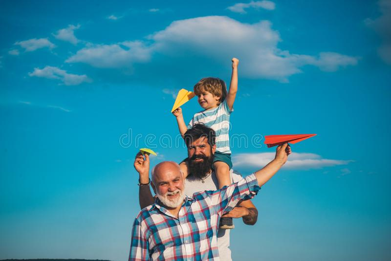 Portrait of happy father giving son piggyback ride on his shoulders and looking up. Dream of flying. Fathers day concept. Generation concept royalty free stock photography