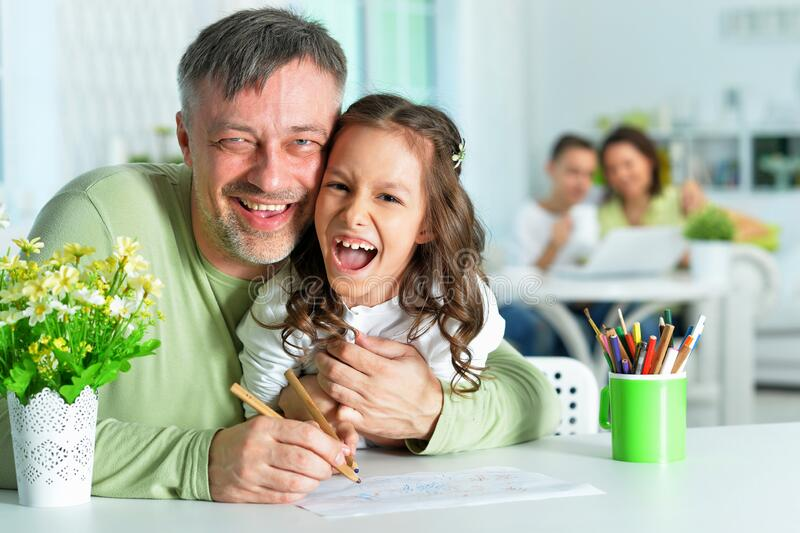 Portrait of happy father and his cute daughter drawing royalty free stock photography