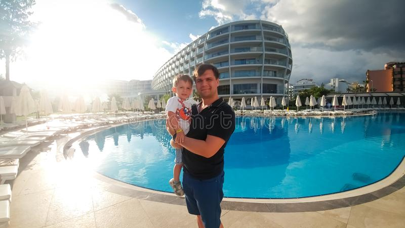 Portrait of happy young father hugging his toddler son against big swimming pool at hotel resort. Family relaxing on stock image