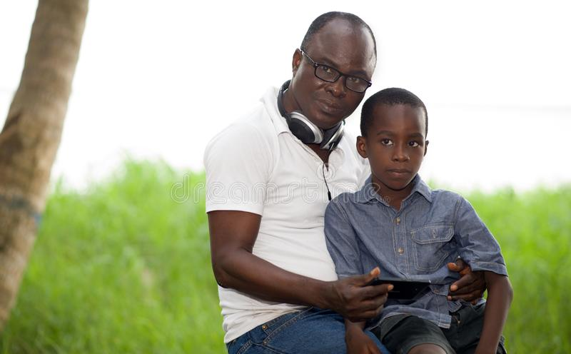 Portrait of happy father and son sitting outdoors. They look aside and listen to music stock image