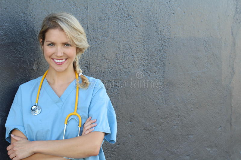Portrait of happy female nurse with stethoscope standing arms crossed isolated over dark gray background royalty free stock images