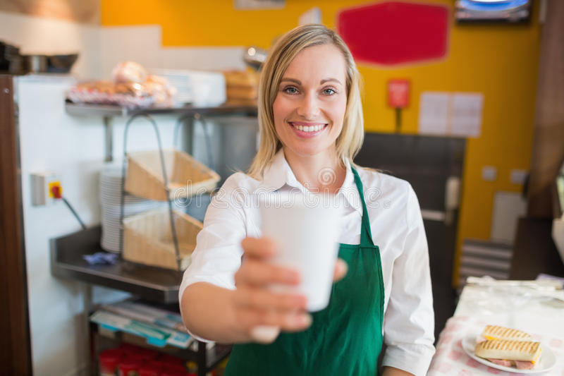Portrait of happy female shop owner holding glass royalty free stock images