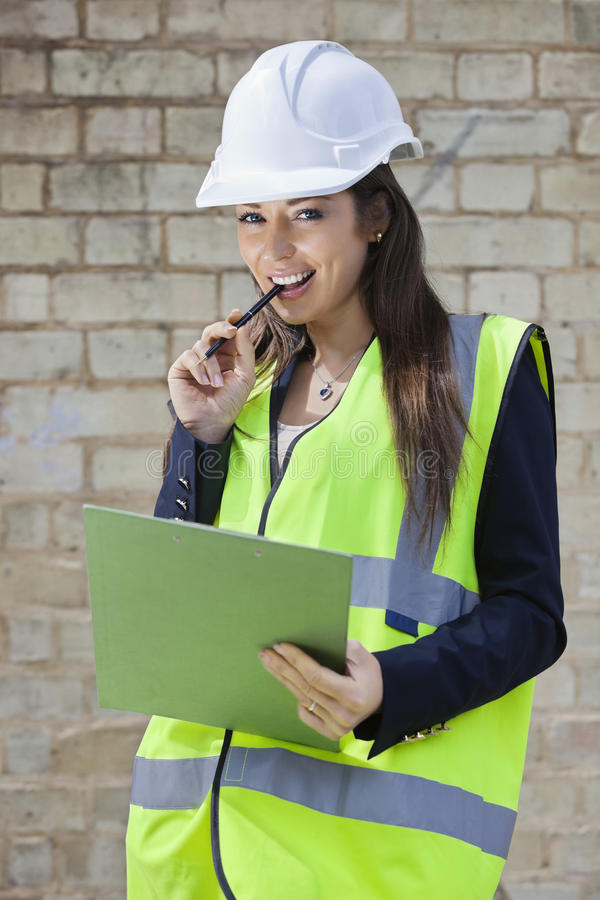 Portrait of a happy female supervisor with clipboard standing at construction site royalty free stock images