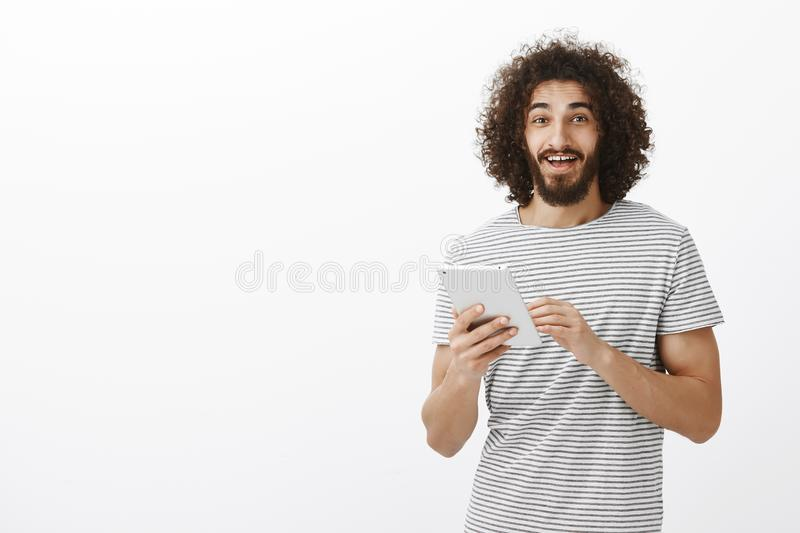 Portrait of happy friendly hispanic bearded man with afro hairstyle, holding white digital tablet and smiling broadly at royalty free stock photos