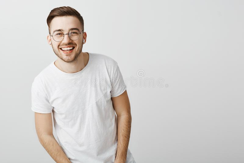 Portrait of happy friendly-looking stylish caucasian guy in glasses and wireless earphones laughing and smiling broadly royalty free stock photo