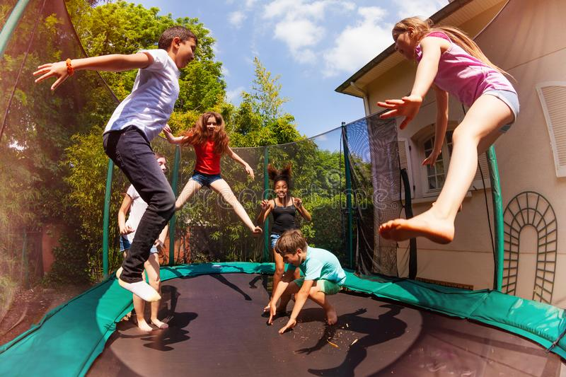 Happy friends jumping on the trampoline in summer. Portrait of happy friends, multiethnic boys and girls, jumping on the backyard trampoline in summer stock image