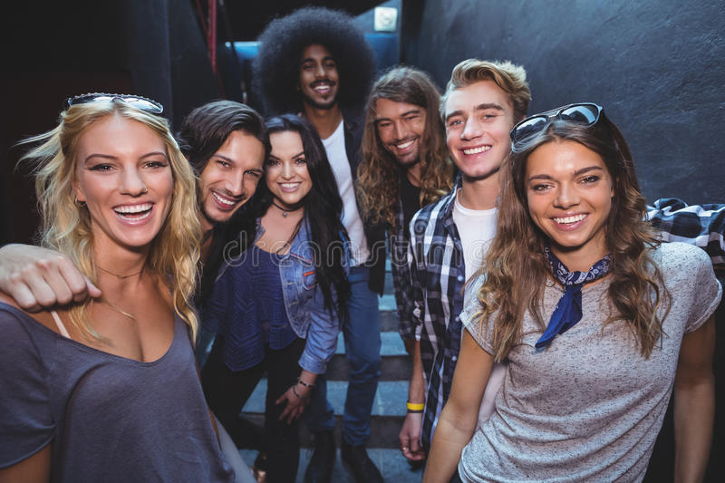 Portrait of happy friends in room. Portrait of happy friends standing in illuminated room at nightclub stock images