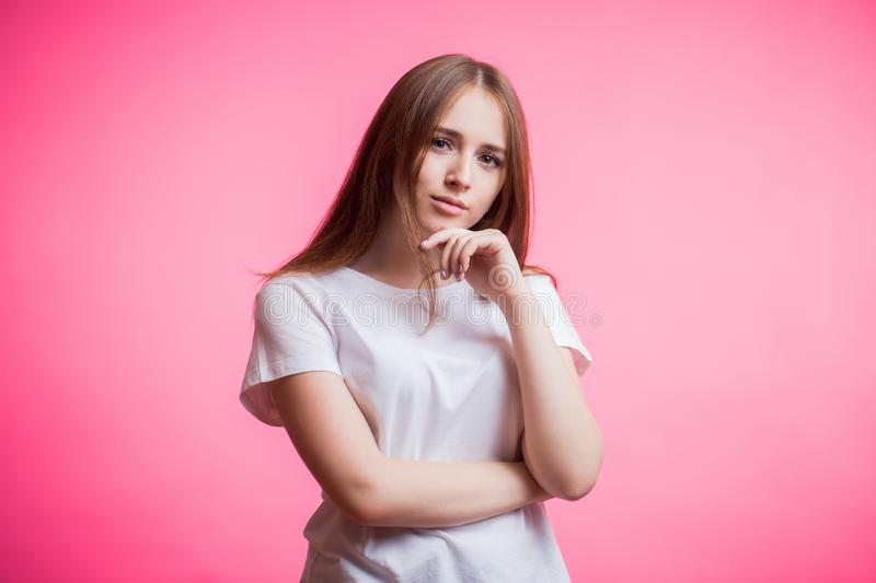 Portrait of happy ginger girl wears a white shirt and smiling looking at camera on a pink background with a copy space. Human royalty free stock photo