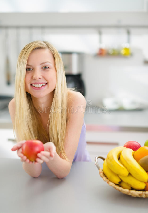 Portrait of happy girl with apple in kitchen stock photography