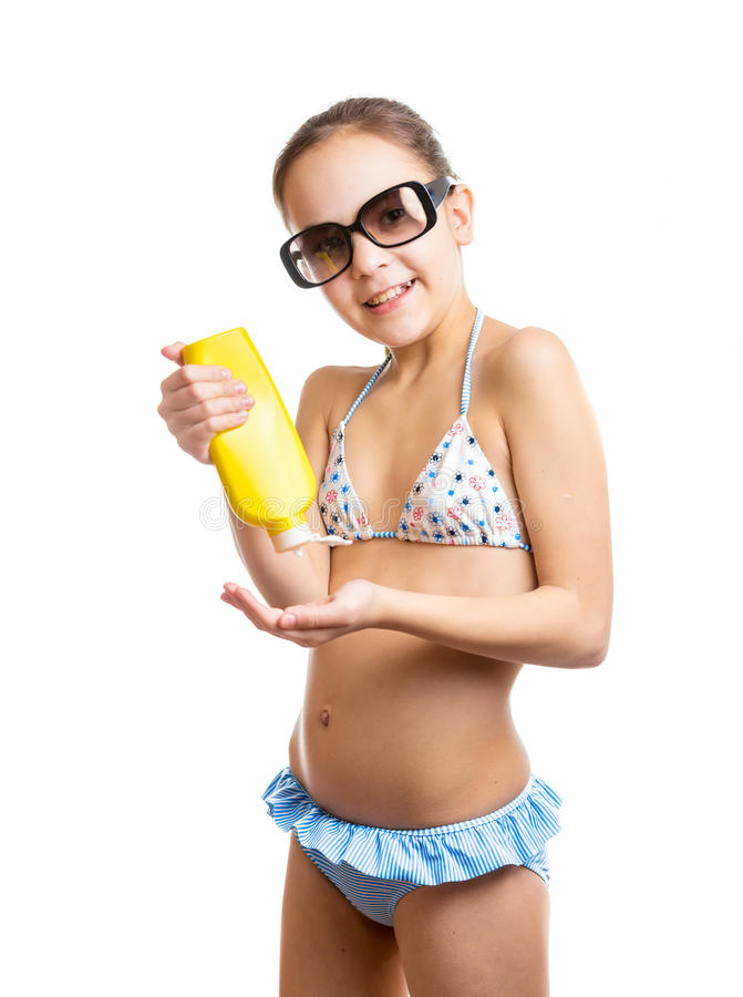 Portrait of happy girl applying suntan lotion royalty free stock photography