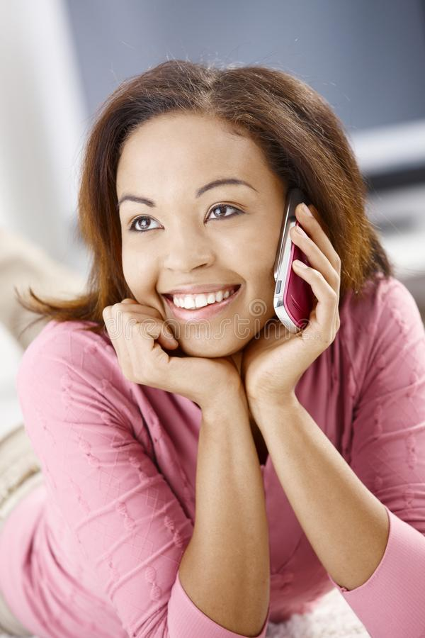 Portrait of happy girl with cell phone. Portrait of cheerful girl using cell phone, smiling happily stock image