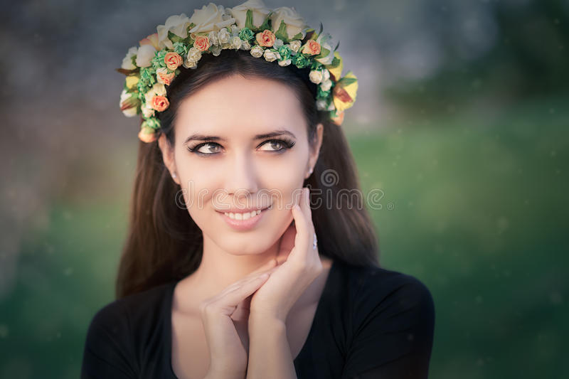 Portrait of a Happy Girl with Floral Wreath Outside. Close-up of a beautiful young woman outside wearing a floral headdress royalty free stock photography