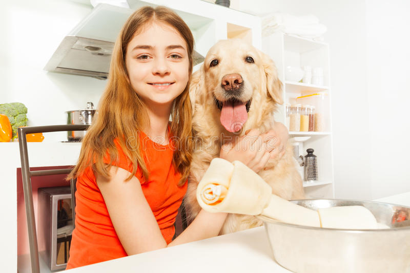 Portrait of happy girl with her pet in the kitchen stock photos