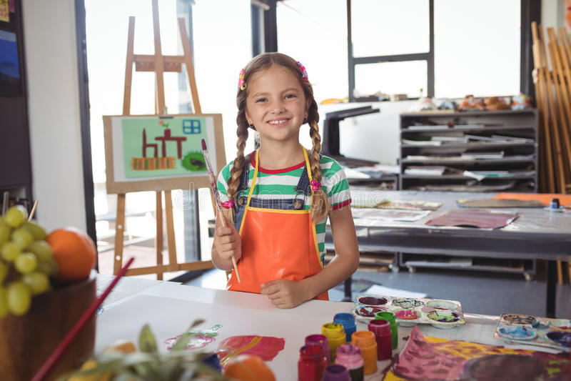 Portrait of happy girl holding paintbrushes royalty free stock photo