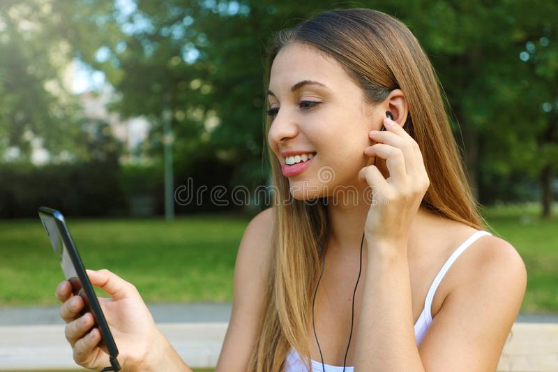 Portrait of a happy girl listening music on line with earphones from a smart phone in the park in a summer sunny day royalty free stock image