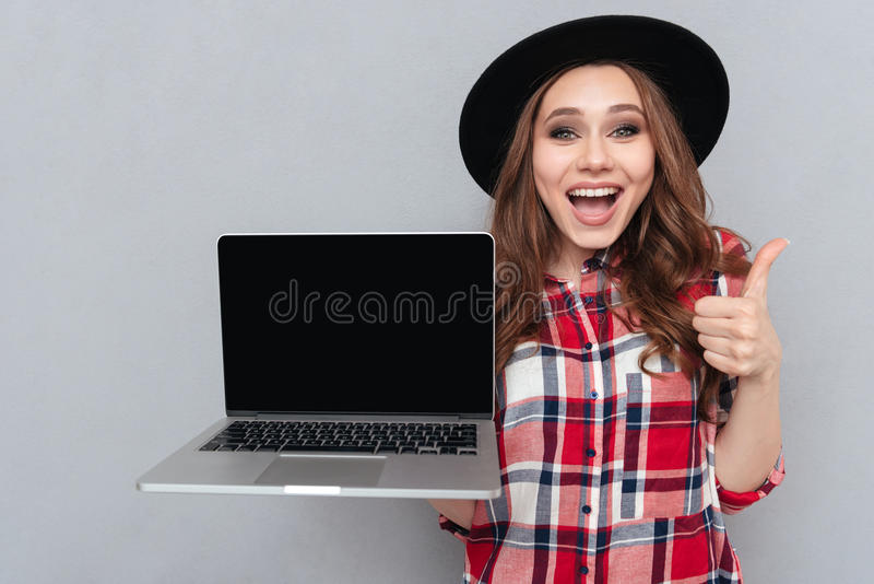Portrait of a happy girl in plaid shirt holding laptop. Portrait of a smiling happy girl in plaid shirt holding blank screen laptop computer and showing thumbs royalty free stock image