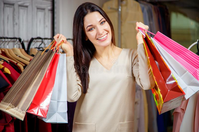 Portrait of a happy girl with purchases. Beautiful woman with shopping bags in a shopping center. Buyer. Sales royalty free stock photography
